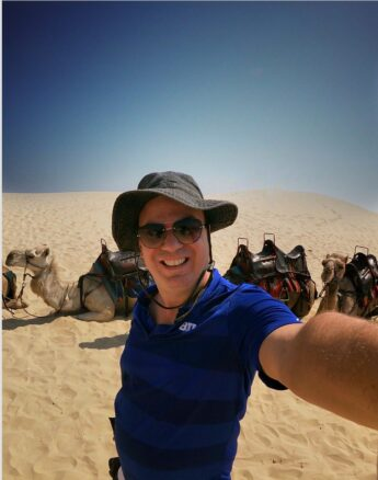 Alex taking a selfie in front of a pack of camels in the sand dunes of Anna Bay, NSW