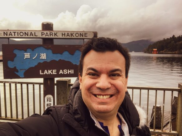Selfie of Alex with the Lake Ashi sign and lake behind him with a cloudy sky