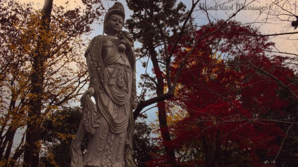 Statue with a red and yellow foliage on the trees