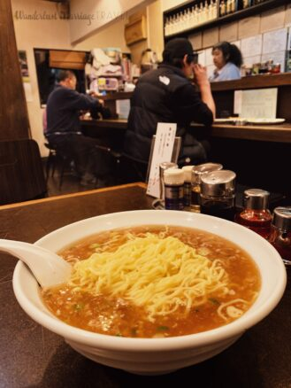 photo of a bowl of ramen, and Japanese men sitting at the bar