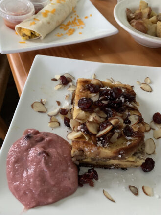 sausage stuffed French toast with raspberry puree, sliced almonds and cranberries