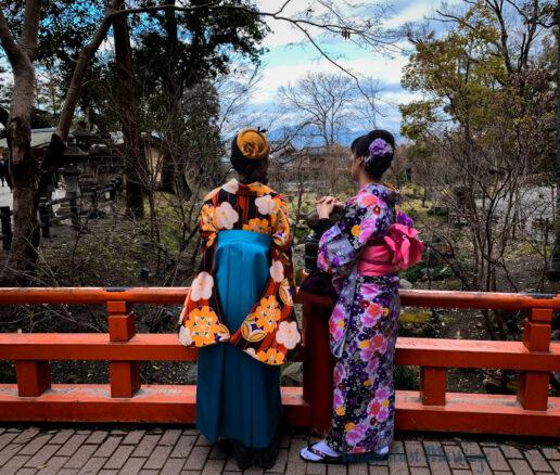 two Japanese women standing on a bridge wearing traditional kimonos