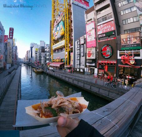 Holding Takoyaki (fried octopus balls) on the Dotonbori Canal in Osaka, Japan