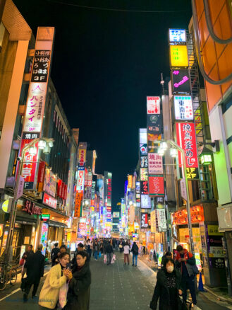 the many shops and bustling crowds of the Shinjuku district in Tokyo, Japan