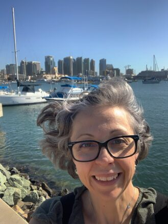 Women with glasses with the bay behind her with boats and skyscrapers