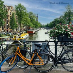 Amsterdam cannel with bikes on a bridge and a blue sky