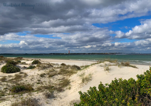 View of the dunes at Smyrna Dunes State Park with the lighthouse in the distance across the inlet