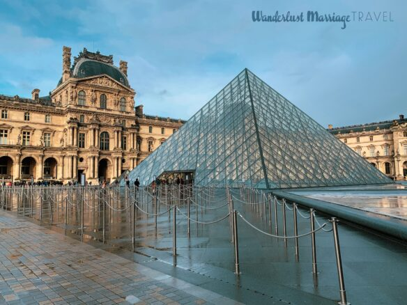 A glass pyramid in front of the Louvre Museum after it has just rained