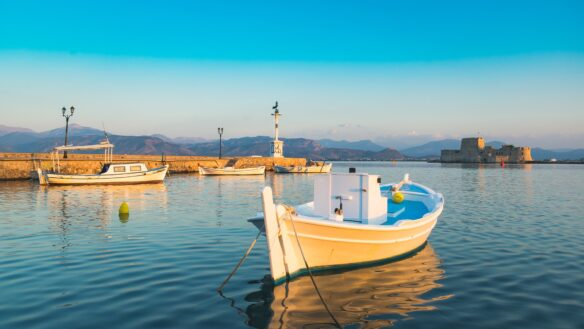 Boat dotting the harbor of Nafplio, Greece with medieval Bourtzi Castle in the background.