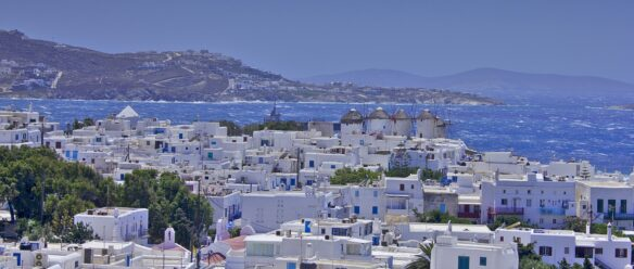 view of the island of Mykonos, including the row of 16th century windmills above the white washed town