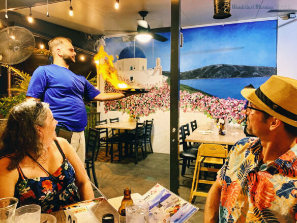 a man and a lady watch the restaurant server holding a plate with cheese on fire with a mural of Greece in the background