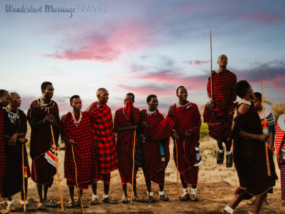 12 Maasai people chanting and one man is jumping high in the air at dusk, the are all dressed in red and black print