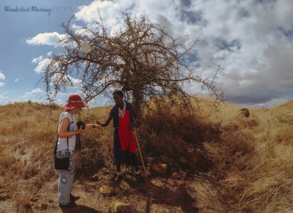 A Maasai warrior is explaining and showing Bell how they use the milk from a certain type of tree on their skin
