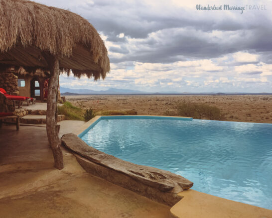 A swimming pool over looking the plains with a cloudy sky