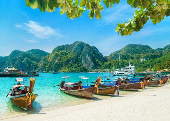 Small wooden boats docked on the shore of the beach, with aqua water, and rocky fjords coming out of the ocean