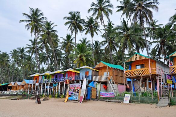 Colorful beach shacks surrounded by palm tress and sand