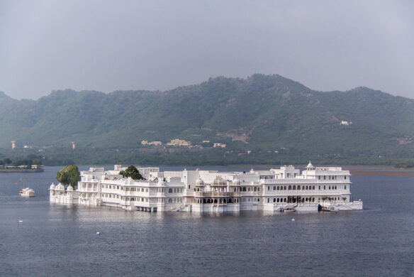 A large white hotel surrounded by a large lake and green mountains in the background