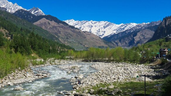 River flowing through a snow capped mountain range with a rocky river bank