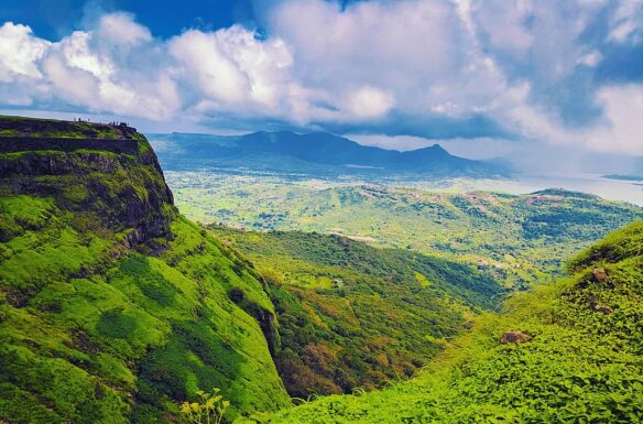 Lush green mountain range, with a blue sky and white clouds